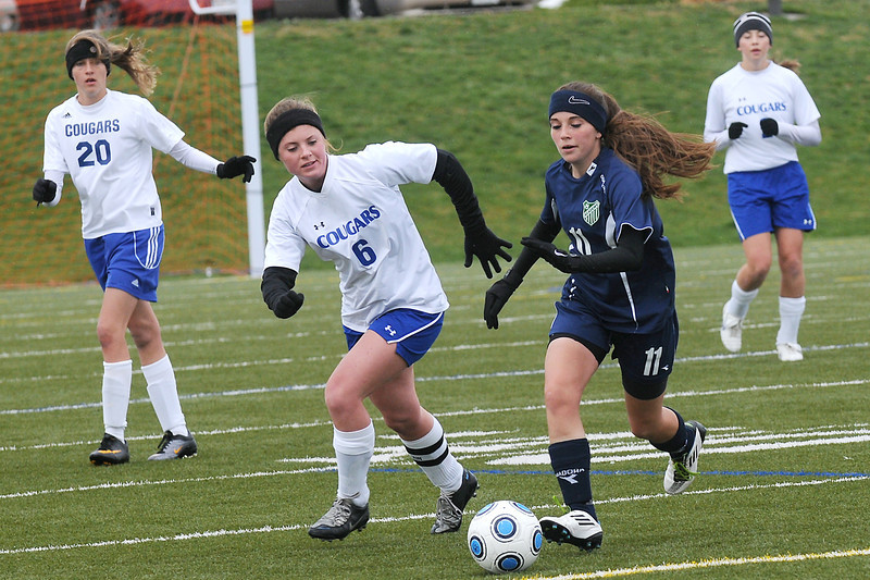 Resurrection Christian School senior Audrey Isabelle (6) and Academy's Vanessa Norton (11) track down the ball while Sarah Wallman (20) and Allison Weaver look on in the first half of their match Wednesday at the Loveland Sports Park.