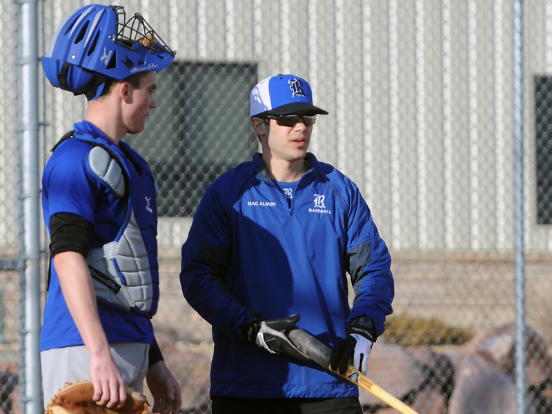 Resurrection Christian School head baseball coach Grant MacAlmon, right, talks to catcher Aaron Gravatt while working on a drill during practice Wednesday, March 6, 2013 at the school.