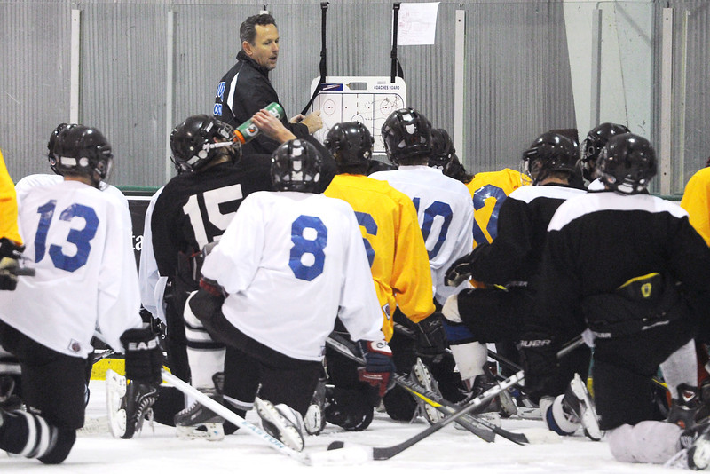 Resurrection Christian School assistant hockey coach Bob Herrfeldt, back, goes over a drill with players during practice on Tuesday, Nov. 27, 2012 at the NoCo Ice Center in Windsor.