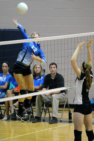 Resurrection Christian School sophomore Preston Lienemann (12) goes up for a spike over Front Range Christian's Dawn Fulkerson during set three of their match Tuesday, Sept. 18, 2012 at RCS.