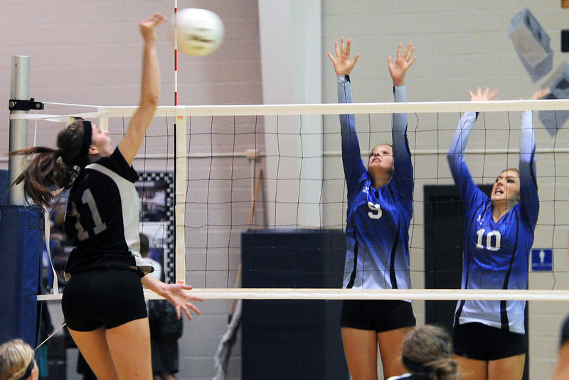 Resurrection Christian School teammates Jennifer Lohr, right, and Madison Webb go up to block a spike by Front Range Christian's Meredith Whatley during their match on Tuesday, Sept. 18, 2012 at RCS.