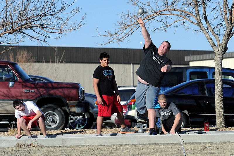 Resurrection Christian School senior Jake Mandos, front, tosses a shot put into a field adjacent to a parking lot at the school during track practice Tuesday, March 6, 2012 while teammates, back from left,  Chase Hawkinson, Julius Padilla and Kyle Burleson look on.