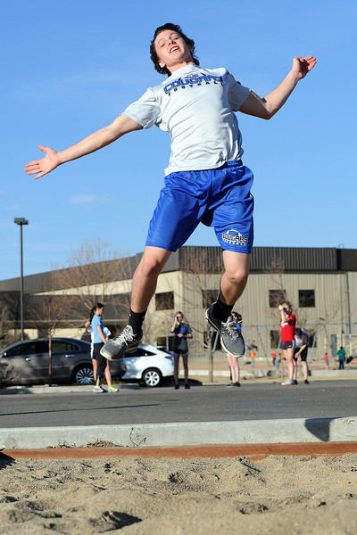Resurrection Christian School junior Trent Buxman flies through the air toward the sand pit while practicing the long jump with other members of the school's track and field team on Tuesday, March 6, 2012.