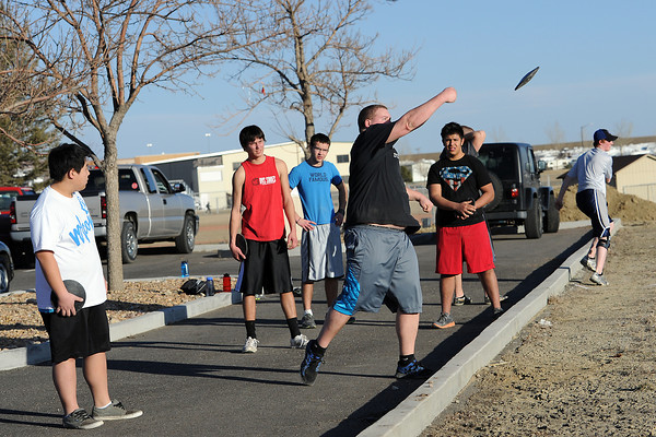 Resurrection Christian School senior Jack Mandos, middle, throws a discus during practice with his track and field teammates on Tuesday, March 6, 2012 outside the school.
