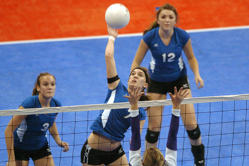 Resurrection Christian School juior Danyelle Barker spikes the ball while teammates Rebekah Moser, left, and Rachel Perry look on during game two of their match against Fowler in the finals of the Class 2A State Volleyball Championships on Saturday, Nov. 14, 2009 at the Denver Coliseum.