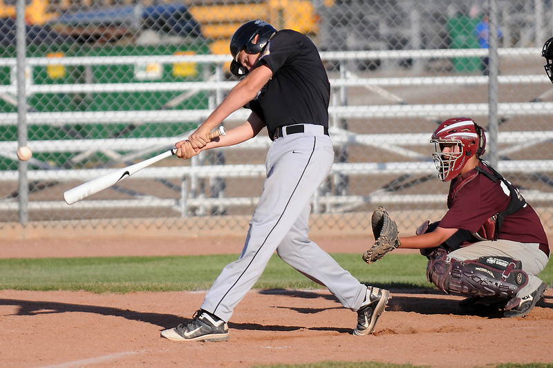 Legion Post 70's Mack Morford laces a double in the bottom of the fourth inning while Berthoud catcher Jackson Lussier looks on during their game Wednesday evening at Roosevelt High School.