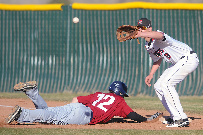 Northridge High School baserunner Jordan Francies dives safely back to first base ahead of the tag by Roosevelt's Nate Trobee on a pickoff attempt in the top of the fifth inning of their game Thursday, March 22, 2012 at RoughRider Ballpark.