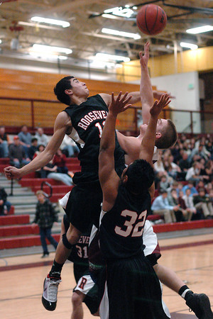 Roosevelt High School senior Tony Predmore, left, defends on a shot attempt by Berthoud's Joel Maly in the second quarter of their game Friday, Dec. 18, 2009 at BHS. The Spartans won, 63-53.
