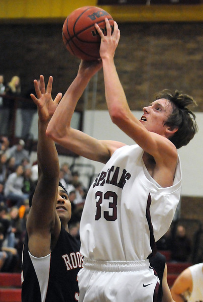 Berthoud High School senior Cameron Botts, right, puts up a shot over Roosevelt's Brandyn Hernandez in the second quarter of their game on Wednesday, Dec. 8, 2010 at BHS. Roosevelt won, 74-45.