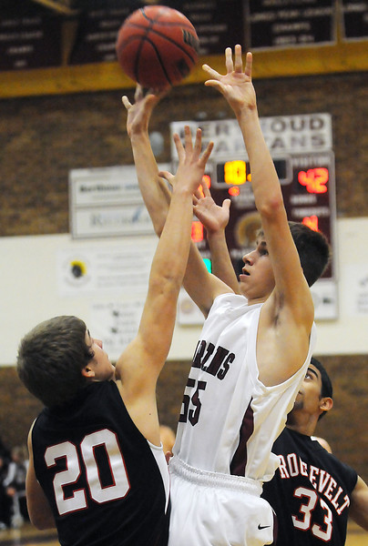 Berthoud High School sophomore Tucker Skoric (55) attempts a shot between Roosevelt's Dylan Cunningham (20) and Raul Martinez (33) in the second quarter of their game on Wednesday, Dec. 8, 2010 at BHS. Roosevelt won, 74-45.
