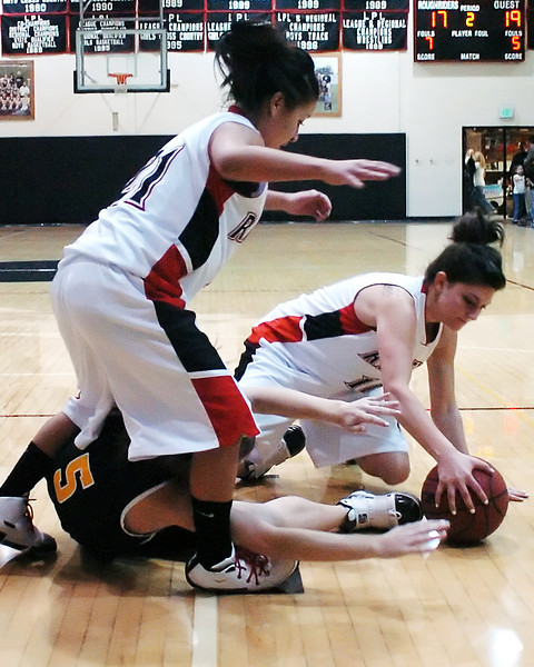 Roosevelt High School's Gabby Ramirez, left, and teammate Kaylee Longoria scramble for a loose ball with Thompson Valley's Lauren Mickelson in the second quarter of their game on Tuesday, Jan. 5, 2010 at RHS.