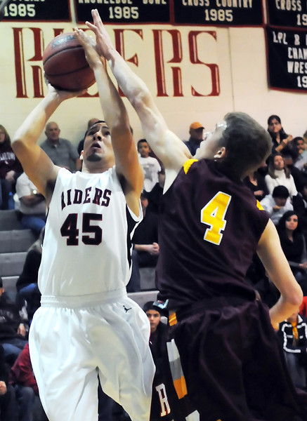 Roosevelt High School senior Fily Perez (45) attempts a shot over Windsor's Connor Ervin (4) in the first quarter of their game on Tuesday, Jan. 11, 2011 at RHS.