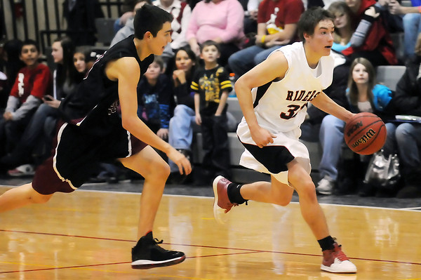 Roosevelt High School senior Sam Strait, right, dribbles around Berthoud defender Ryan Vasquez in the fourth quarter of their game Tuesday at RHS. The RoughRiders won, 76-59.