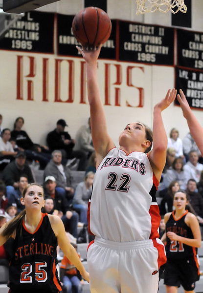 Roosevelt High School junior Tiffany Trimble (22) puts up a shot while Sterling's Tyler Chrisman (25) and Jami Szczepanski (21) look on in the second quarter of their game on Tuesday, Jan. 18, 2011 at RHS.