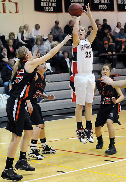 Roosevelt High School senior Kaitlin Flynn, center, shoots a jump shot in front of Sterling players, from left,  Tyler Chrisman and Morgan Colburn and Paige Locke, right, in the first quarter of their game on Tuesday, Jan. 18, 2011 at RHS.