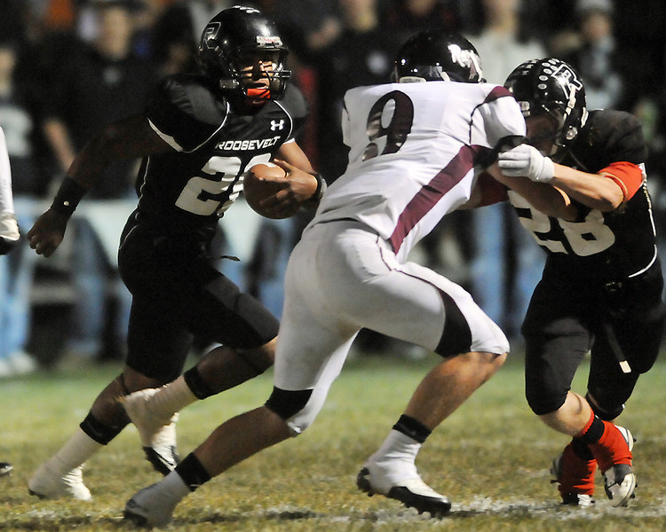 Roosevelt High School quarterback Brandyn Hernandez, left, runs behind the the block of teammate Christian Kratz in the first quarter of their game against Silver Creek on Friday at Peterson Stadium in Johnstown.