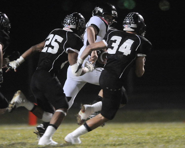 Silver Creek High School's Ian McNabb makes a carry in front of Roosevelt defenders Juan Sanchez (25) and Joshua Semmler in the first quarter of their game Friday, Nov. 5, 2010 at Peterson Stadium in Johnstown.