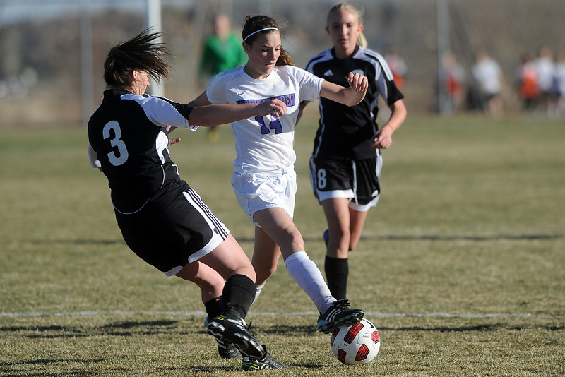Mountain View High School's Leigh McDonald, middle, battles with Roosevelt's Sydney Jacox, left, and Hannah Brendemihl for control of the ball during their game Wednesday, March 21, 2012 at MVHS.