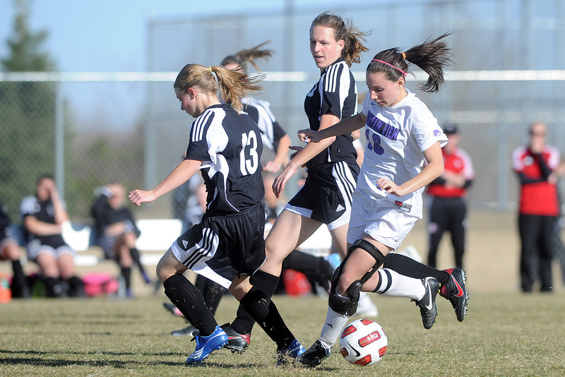 Mountain View High School's Emily McFeron, right, battles for control of the ball with Roosevelt's Cassi Ballard and Jessica Meek during their game on Wednesday, March 21, 2012 at MVHS.