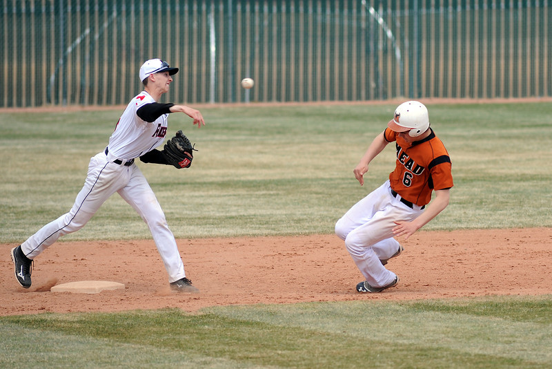 Roosevelt High School shortstop AJ Clayton, left, makes the throw to first on a double play attempt after getting the force out of Mead baserunner Kyle Couch in the top of the sixth inning of their game Saturday, March 30, 2013 at RHS.