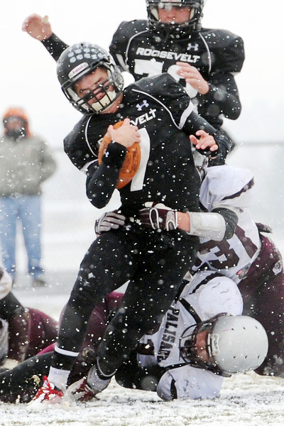 Roosevelt High School quarterback Spencer Urban is tackled by Palisade defenders Clay Young, bottom, and Dalton Hannigan in the second quarter of their game on Saturday, Nov. 10, 2012 at Peterson Field.