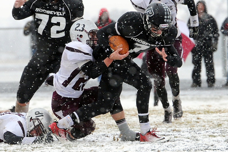 Roosevelt High School quarterback Spencer Urban is tackled by Palisade defenders Clay Young, bottom left, and Dalton Hannigan in the second quarter of their game on Saturday, Nov. 10, 2012 at Peterson Field.
