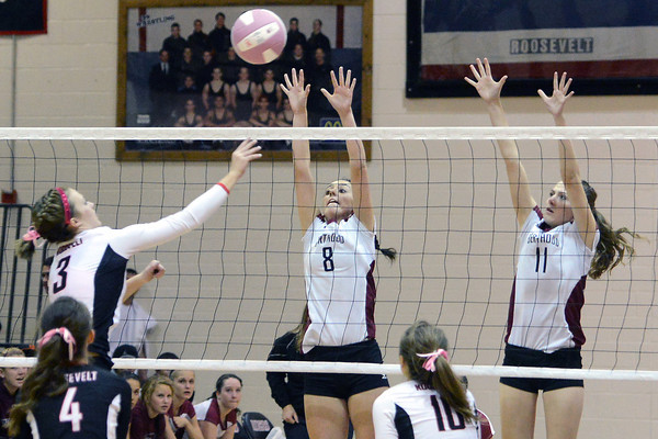 Berthoud High School's Madi White, right, and Lynda Hutchins go up at the net against Roosevelt's Whitney Shawver (3) during set one of their match on Tuesday, Oct. 9, 2012 at RHS. The RoughRiders won, 3-1.