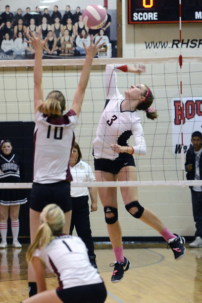 Roosevelt High School's Whitney Shawver (3) spikes the ball against Berthoud's Hannah Atkinson (10) while Haley Hummel (1) looks on during set one of their match on Tuesday, Oct. 9, 2012 at RHS. The RoughRiders won, 3-1.