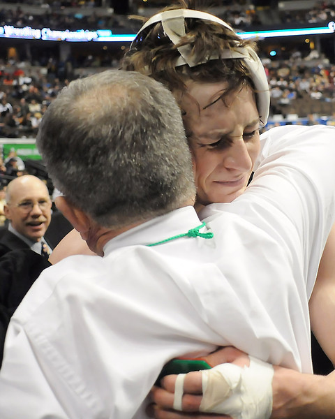 Roosevelt High School senior Blake Nygren hugs head wrestling coach Mike Pallotto after defeating Northridge's Robert Pickrell in the Class 4A 160-pound final match of the State Wrestling Championships on Saturday at the Pepsi Center in Denver.