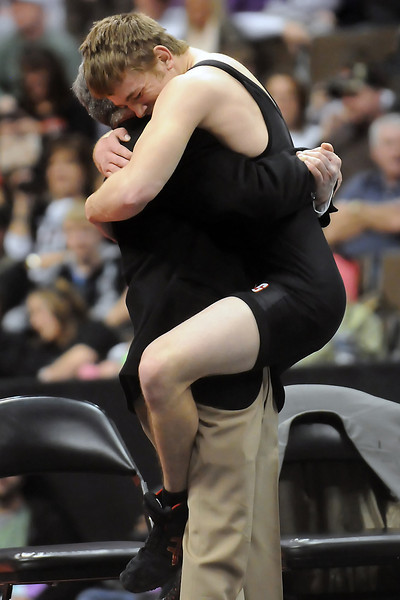 Roosevelt High School's C.J. York gets a hug from head coach Mike Pallotto after defeating Montrose's Drew Schumann in the 130-pound final of the Class 4A State Wrestling Tournament on Saturday at the Pepsi Center in Denver.