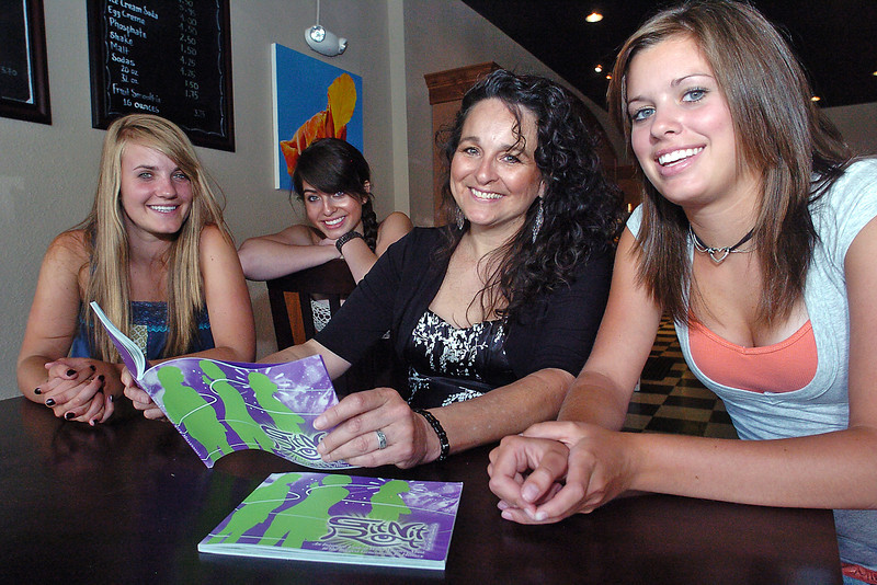 "Loveland author Deloris Valdez Jarvis holds a copy of her book, ""GitNit Right With Millenials"" as she sits for a portrait Tuesday at Sweet Spot in downtown Loveland with several young women who are featured in the book. From left are Ellie Johnson, 16, Kaitlyn Amick, 15, Jarvis, and Tanna Chandler, 16."