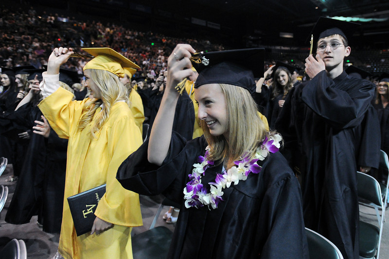 Thompson Valley High School's Camille McLaughlin, front, and other seniors move the tassels on their mortar board hats at the end of the school's graduation ceremony on Saturday, May 25, 2013 at the Budweiser Events Center.