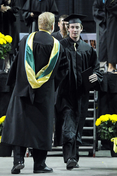 Thompson Valley High School's Jonny Pomerleau, right, shakes hands with principal Mark Johnson after picking up his diploma during graduation on Saturday, May 25, 2013 at the Budweiser Events Center.