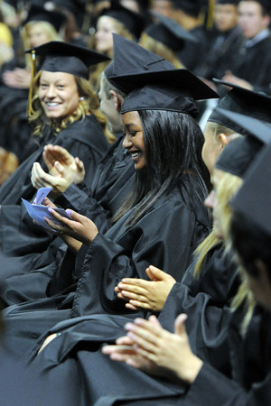Thompson Valley High School's Emlynn Mee, middle, looks in an envelope that was taped under her chair which contained a $100 bill during the school's graduation ceremony on Saturday, May 25, 2013 at the Budweiser Events Center.