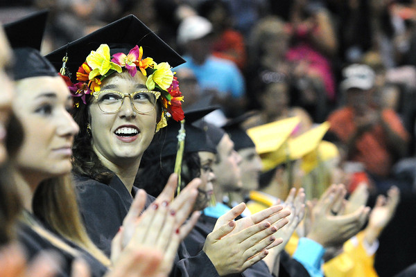Thompson Valley High School's Anastasia Mayhew dons a ring of flowers on her mortar board while sitting with classmates during their graduation ceremony on Saturday, May 25, 2013 at the Budweiser Events Center.