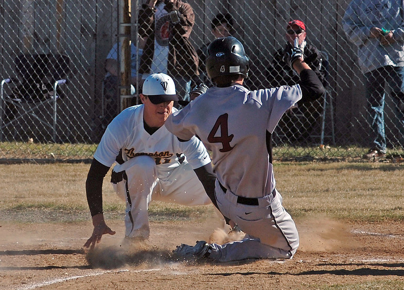 Thompson Valley's Caleb Carlson #11 tags out Silver Creek's #4 at home during their game Thursday.