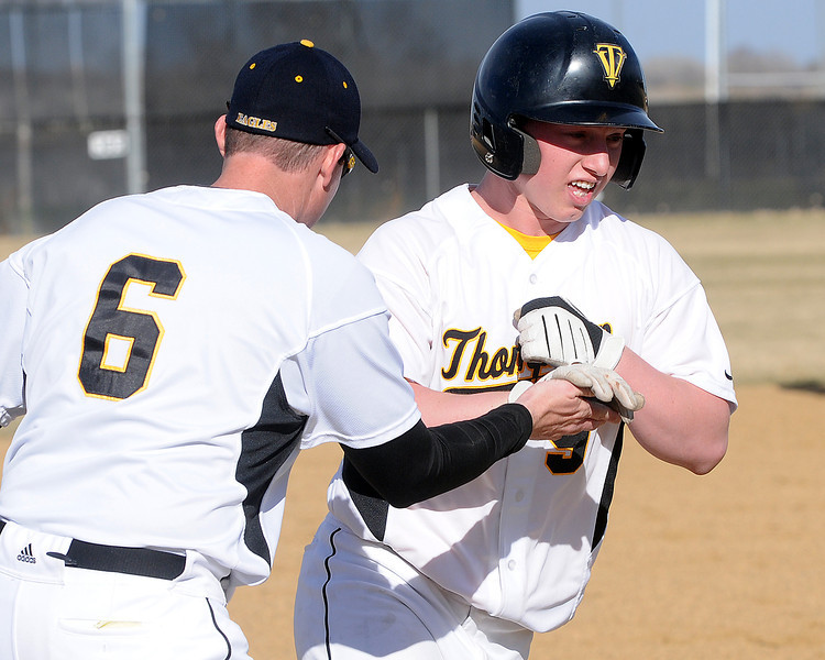 Thompson Valley High School's Kyle Kelly is congratulated by coach Jay Denning after hitting a home run during a game against Northridge on Tuesday, March 30, 2010 at Constanz Field. The Eagles lost, 19-11.