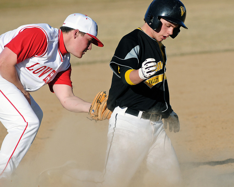 Thompson Valley High School's Max Schoen slides safely into third base for a triple in front of the tag attempt by Loveland's Drew Posegate in the top of the fifth inning of their game on Tuesday, March 16, 2010 at Swift Field. Loveland won, 14-4, in the fifth inning.