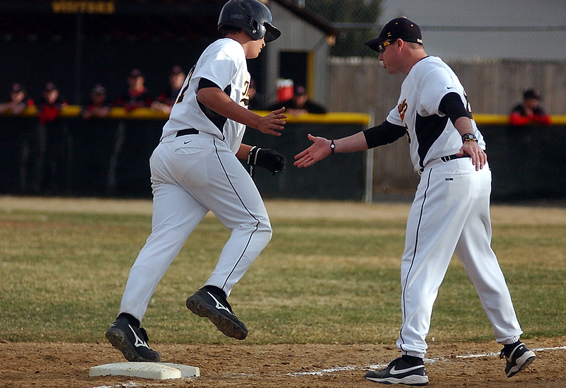 Basecoach(#6) congratulates #17 on his homerun, leaving the score 11-7 (home) in the sixth inning.