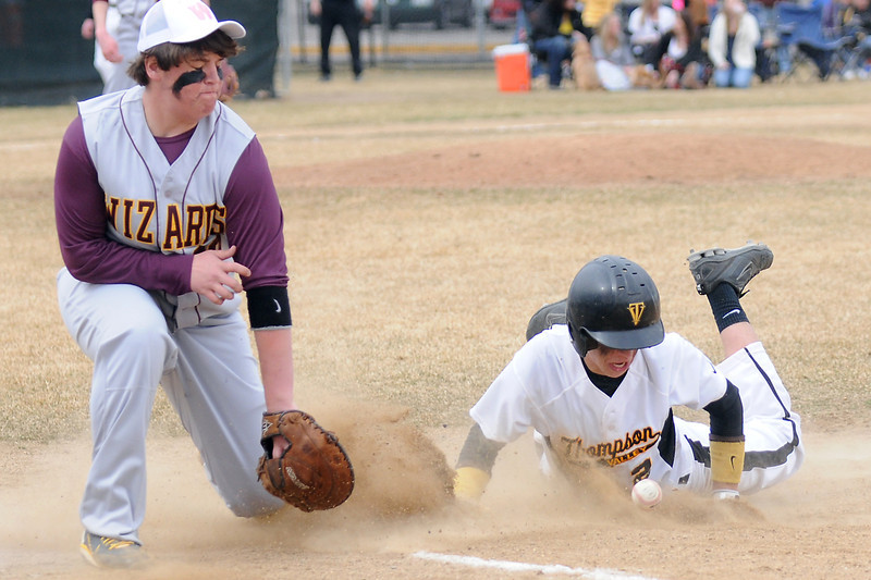 Thompson Valley High School's Chris Sievers, right, dives back to the bag ahead of the throw to Windsor first baseman D.J. Knott in the bottom of the fifth inning on Saturday, March 12, 2011 at Constantz Field. The Eagles lost, 3-2.