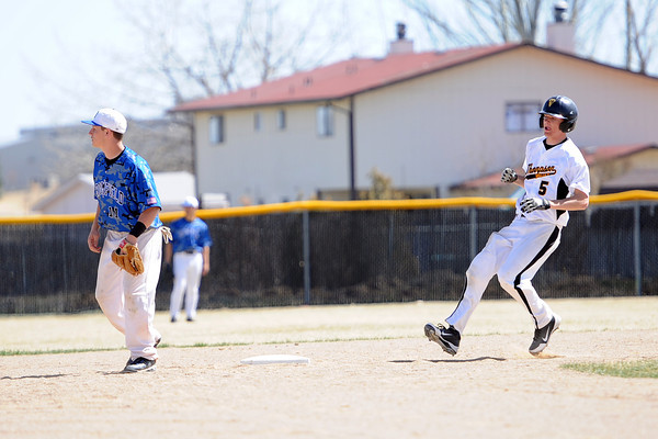 Thompson Valley High School senior Cole Mueller, right, holds up a second base for a double ahead of the throw to Broomfield's Jordan Arensdorf in the bottom of the fifth inning of their game Saturday, March 24, 2012 at Constantz Field.