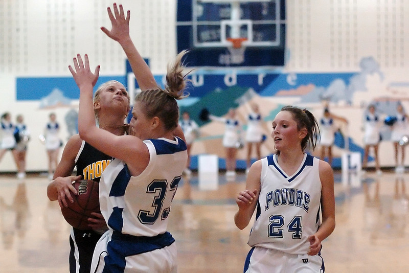 Thompson Valley High School senior Sydney Paulsen, left, collides with Poudre's Danielle Mayer while Kaelee Hewett looks on during their game on Tuesday, Dec. 1, 2009 at PHS.