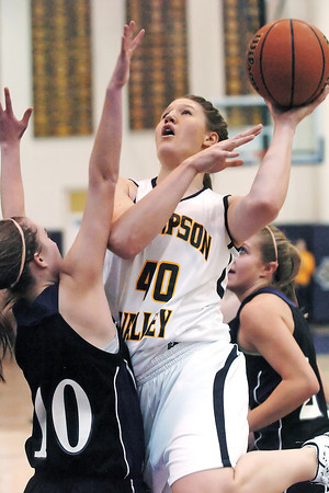Thompson Valley High School junior Jordan Sibrel goes up for a shot between Mountain View defenders Katie Wilson, left, and Rikelle Berry in the second quarter of their game on Saturday, Dec. 5, 2009 at Fort Collins High School.