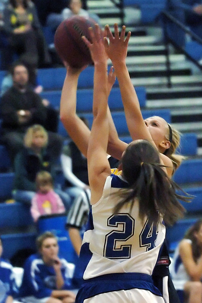 Thompson Valley High School senior Sydney Paulsen takes a shot over the outstretched hands of Poudre's Kaelee Hewett in the first quarter of their game  on Tuesday, Dec. 1, 2009 at PHS.