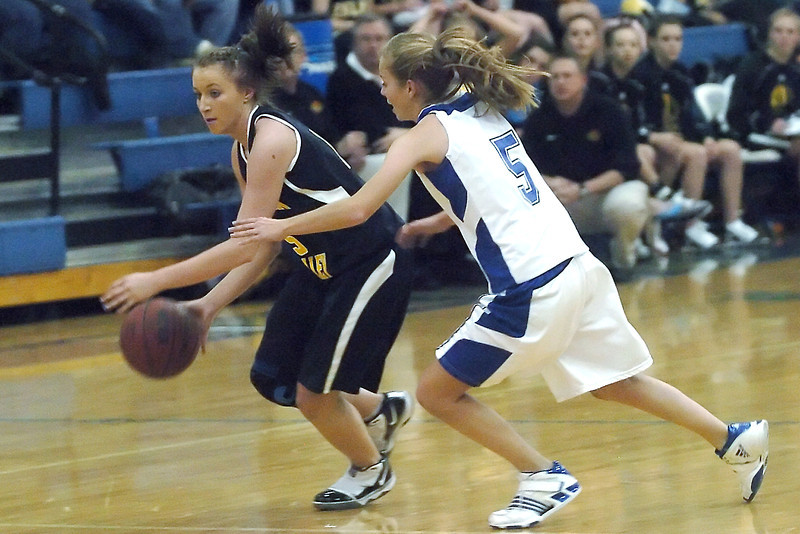 Thompson Valley High School junior Kenzie Archer drives around Poudre defender Madison Hunt in the first quarter of their game on Tuesday, Dec. 1, 2009 at PHS.