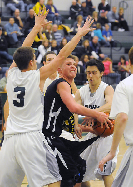 Thompson Valley High School freshman Austin Dyer, center, is pressured by Fossil Ridge defenders in the second quarter of their game Thursday at FRHS.
