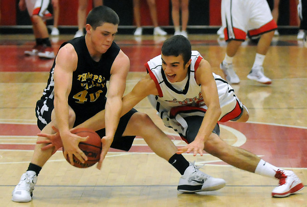 Thompson Valley High School senior Caleb Carlson, left, and Loveland's Darius Coldiron track down a loose ball in the first quarter of their game on Friday, Dec. 3, 2010 at LHS.