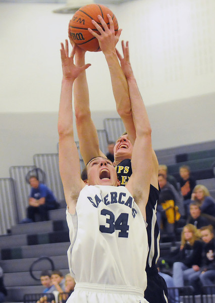 Thompson Valley High School junior Karsen Buschjost, back, pulls down a rebound over Fossil Ridge's Alex Blum in the second quarter of their game Thursday at FRHS.