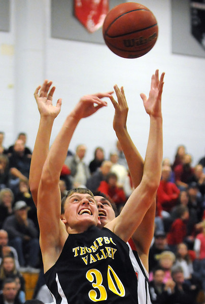 Thompson Valley High School junior Karsen Buschjost (30) and Loveland senior Jim Etling battle for a rebound in the first quarter of their game on Friday, Dec. 3, 2010 at LHS.