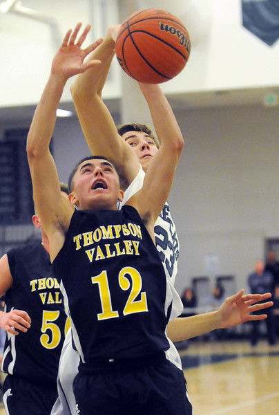 Thompson Valley High School junior Sheldon Findley (12) has his shot blocked from behind by Fossil Ridge's Clayton Kuchta in the second quarter of their game Thursday at FRHS.